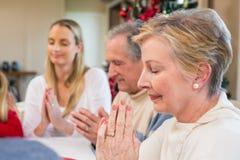 Uitgebreide familie die gunst zeggen vóór Kerstmisdiner stock afbeelding