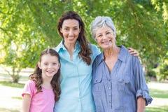 Uitgebreide familie die in het park glimlachen Royalty-vrije Stock Afbeeldingen