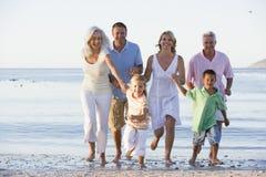 Uitgebreide familie die op strand loopt stock foto's