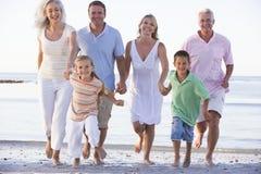 Uitgebreide familie die op strand loopt Stock Foto