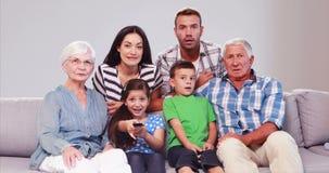 Uitgebreide familie die op TV letten terwijl het veranderen van kanalen stock video
