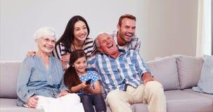 Uitgebreide familie die terwijl het letten van op TV lachen stock video