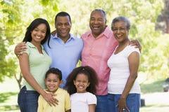 Uitgebreide familie die zich in park het glimlachen bevindt Stock Afbeelding