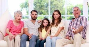 Uitgebreide familie het letten op televisie op de bank stock video