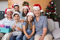 Uitgebreide familie in Kerstmishoeden met giftdozen in woonkamer royalty-vrije stock afbeeldingen