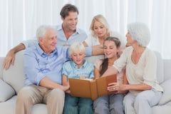 Uitgebreide vrolijke familie die een fotoalbum bekijken royalty-vrije stock afbeelding