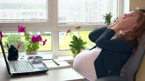 Uitgeputte aanstaande moeder die hoofdpijnzitting in bureau voelen stock videobeelden