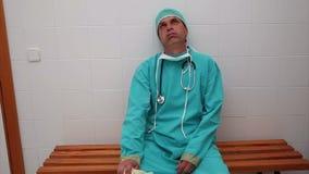 Uitgeputte chirurgenzitting op een bank stock videobeelden