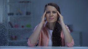Uitgeputte dame die op middelbare leeftijd tempels achter regenachtig venster, migrainepijn masseren stock video