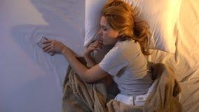 Uitgeputte dame die wekker uitzetten op smartphonegebrek aan energie, slaperige stemming stock videobeelden