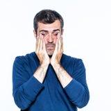 Uitgeputte gebaarde mens die aan hoofdpijn, wat betreft zijn vermoeide ogen lijden stock afbeeldingen