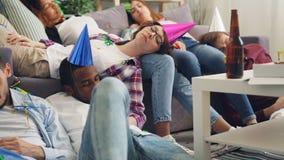Uitgeputte meisjes en kerels die op vloer en bank na partij in flat slapen stock footage