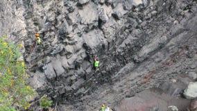 Uitgeputte Rotsklimmer die Baan op Basaltrots evalueren stock videobeelden