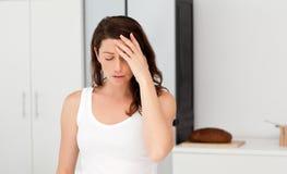 Uitgeputte vrouw die een hoofdpijn in haar badkamers heeft royalty-vrije stock afbeelding