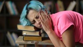 Uitgeputte vrouwelijke student die op stapel van boeken dutten stock footage