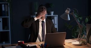 Uitgeputte zakenman die laat - nacht in bureau werken stock video