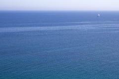 Uitgestrektheid van blauw water van overzees met een witte zeilboot aan horizon Royalty-vrije Stock Fotografie