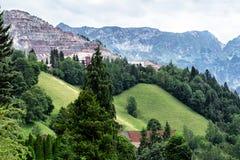 Uitgraving van een mijnbouwbedrijf in de vorm van een piramide tegen de achtergrond van bergen en alpiene weiden royalty-vrije stock foto