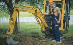 Uitgravingsconcept Mens in werking gesteld graafwerktuig voor gronduitgraving Het graafexploitantwerk aangaande uitgravingsplaats royalty-vrije stock afbeelding