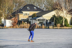 Uithoorn, Netherlands, February 4, 2017 - Ice Skaing on the frozen pond. Man is ice skaing on the small frozen pond Stock Image