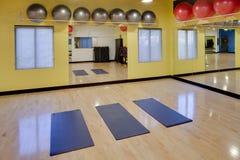Uitrekkende matten en oefeningsballen in gymnastiek Stock Afbeeldingen