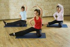 Uitrekkende oefeningen op yogamat Stock Foto's
