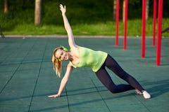 Uitrekkende pasvorm of dansersvrouw die oefening in de grond van trainingsporten doen stock fotografie