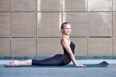 Uitrekkende Vrouw geschiktheid of turner of danser die oefeningen op de bruine stedelijke achtergrond van de muurstad doen stock fotografie