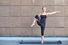 Uitrekkende Vrouw geschiktheid of turner of danser die oefeningen op de bruine stedelijke achtergrond van de muurstad doen stock afbeeldingen