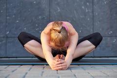 Uitrekkende Vrouw geschiktheid of turner of danser die oefeningen op grijze muur uban achtergrond doen stock foto