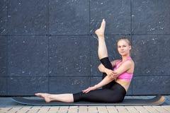 Uitrekkende Vrouw geschiktheid of turner of danser die oefeningen op grijze muur uban achtergrond doen royalty-vrije stock afbeelding