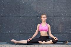 Uitrekkende Vrouw geschiktheid of turner of danser die oefeningen op grijze muur uban achtergrond doen stock fotografie