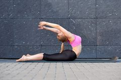 Uitrekkende Vrouw geschiktheid of turner of danser die oefeningen op grijze muur uban achtergrond doen stock foto's