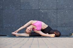 Uitrekkende Vrouw geschiktheid of turner of danser die oefeningen op grijze muur uban achtergrond doen stock afbeeldingen