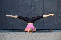 Uitrekkende Vrouw geschiktheid of turner of danser die oefeningen op grijze muur uban achtergrond doen royalty-vrije stock afbeeldingen