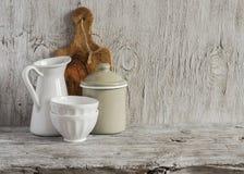 Uitstekend aardewerk - emailkruik, geëmailleerde kruik, witte ceramische kom en olijf scherpe raad op heldere houten oppervlakte Royalty-vrije Stock Foto