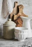 Uitstekend aardewerk en keukengerei - ceramische kommen, geëmailleerde kruik en container, scherpe raadsolijf Stock Foto
