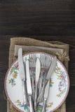 Uitstekend bestek en aardewerk op doeken op rustieke houten backgrou Stock Afbeelding