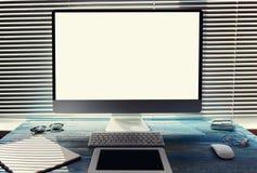In uitstekend blauw is de houten lijst een PC-computer, een tablet en een notitieboekje voor verslagen Stock Foto's