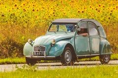 Uitstekend Citroën 2CV voor een gebied met bloeiende zonnebloemen Stock Afbeeldingen
