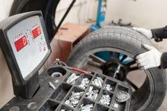 Uitstekend in evenwicht brengend Wiel op nul De technicus spint een autowiel Het hulpmiddel voor reparatie - leid kleine gewichte stock foto