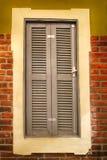 Uitstekend houten Europees venster Uitstekend venster met grijze geschilderde zonneblinden stock afbeeldingen