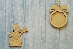 Uitstekend houten speelgoed De sneeuwman met bezem en de bal op gouden koord op lichte achtergrond stileerden sneeuwvlokken stock afbeeldingen