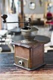 Uitstekend koffiezetapparaat op houten lijst over koffieachtergrond royalty-vrije stock afbeeldingen
