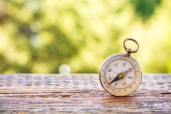 Uitstekend kompas op houten lijst en bokeh achtergrond Royalty-vrije Stock Foto