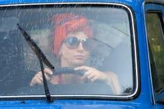 Uitstekend meisje in auto onder regen Stock Afbeeldingen