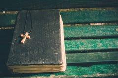 Uitstekend oud heilig bijbelboek, grunge geweven dekking met houten christelijk kruis Retro gestileerd beeld op houten achtergron Stock Fotografie