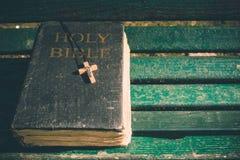 Uitstekend oud heilig bijbelboek, grunge geweven dekking met houten christelijk kruis Retro gestileerd beeld op houten achtergron Stock Afbeelding