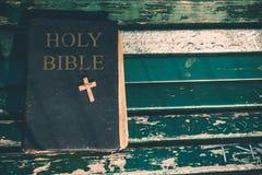Uitstekend oud heilig bijbelboek, grunge geweven dekking met houten christelijk kruis Retro gestileerd beeld op houten achtergron Royalty-vrije Stock Afbeeldingen