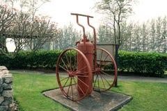 Uitstekend rood brandblusapparaat, ntique rode brand extinguishe op groene tuin stock fotografie